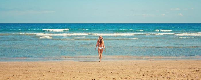 Mulher na praia cheia de amor próprio e auto estima, mudando de vida