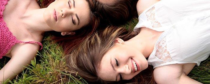 Amigas deitadas na grama e felizes depois de ler a mensagem de aniversário para amiga